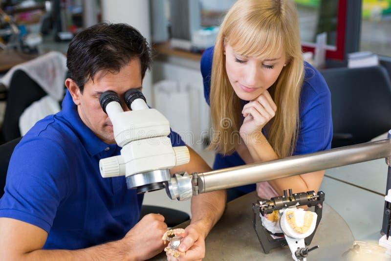 Técnicos dentales que trabajan en el microscopio imagen de archivo