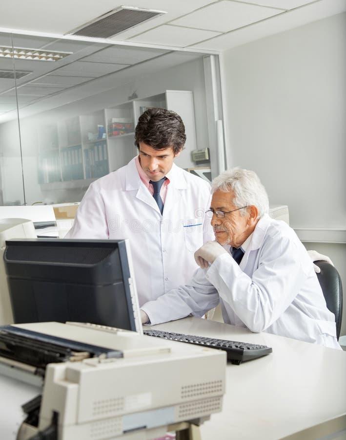 Técnicos que discuten sobre el ordenador fotografía de archivo