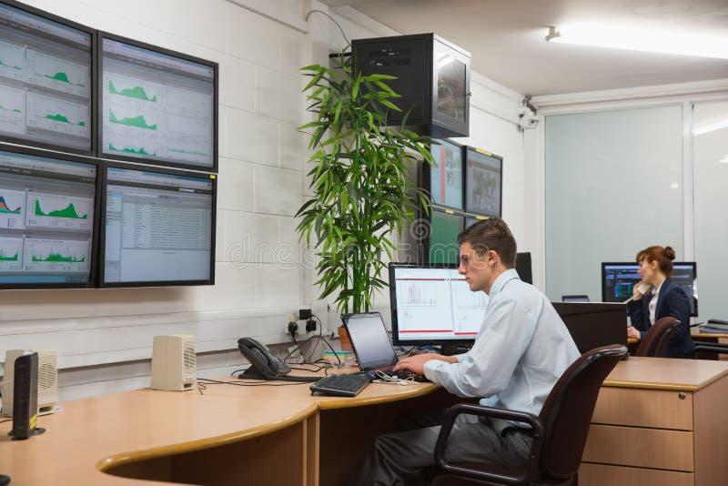 Técnicos que sentam-se em diagnósticos running do escritório fotografia de stock royalty free