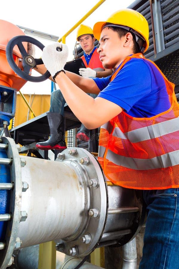 Técnicos que trabalham na válvula na fábrica ou na utilidade fotografia de stock