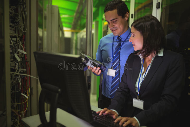 Técnicos que usam o analisador digital do cabo ao trabalhar no computador pessoal fotos de stock royalty free