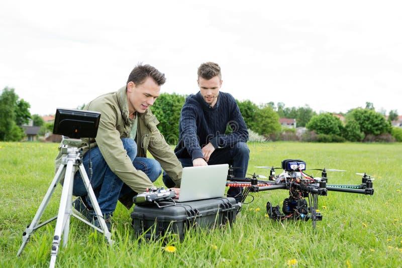 Técnicos que usam o portátil pelo tripé e pelo UAV imagens de stock