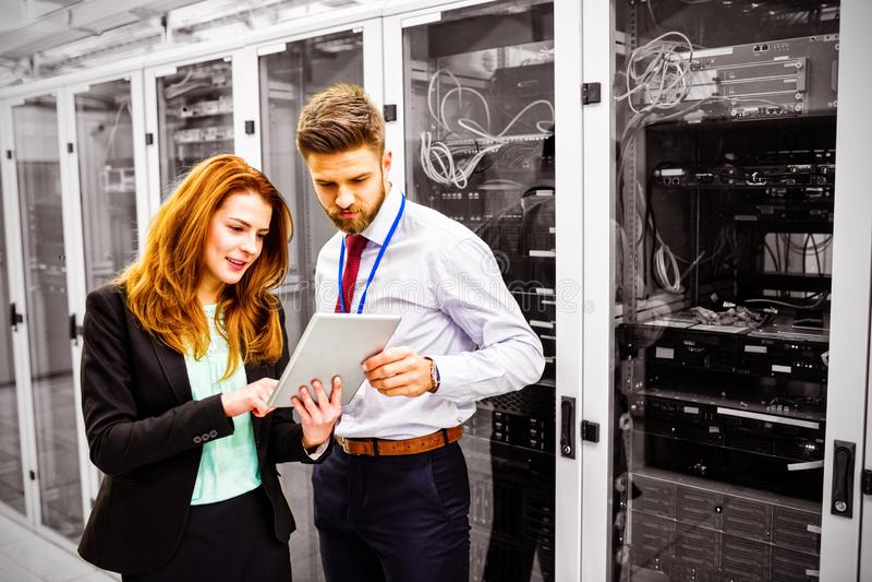 Técnicos que usan la tableta digital mientras que analiza el servidor fotos de archivo libres de regalías
