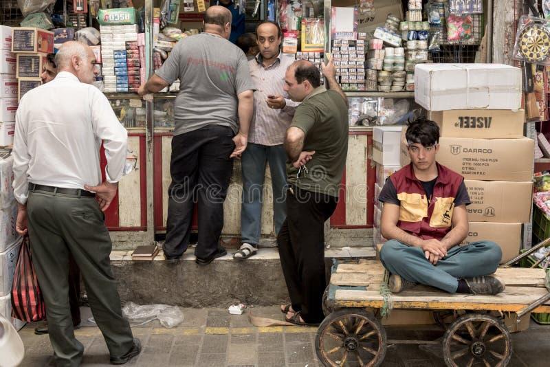 TÉHÉRAN, IRAN - 14 AOÛT 2016 : Les négociants et garçons de livraison ayant une coupure et la discutant dans une rue couverte de  photos libres de droits