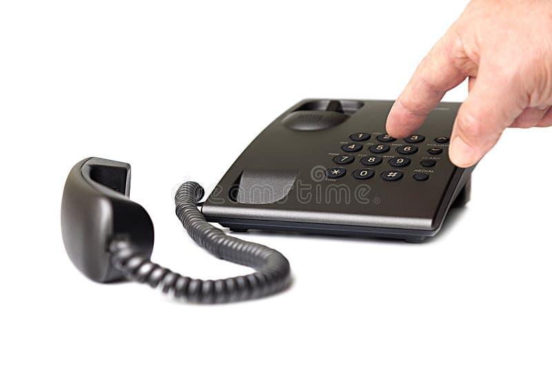 Téléphone à bouton-poussoir noir et la main qui compose le numéro photos libres de droits