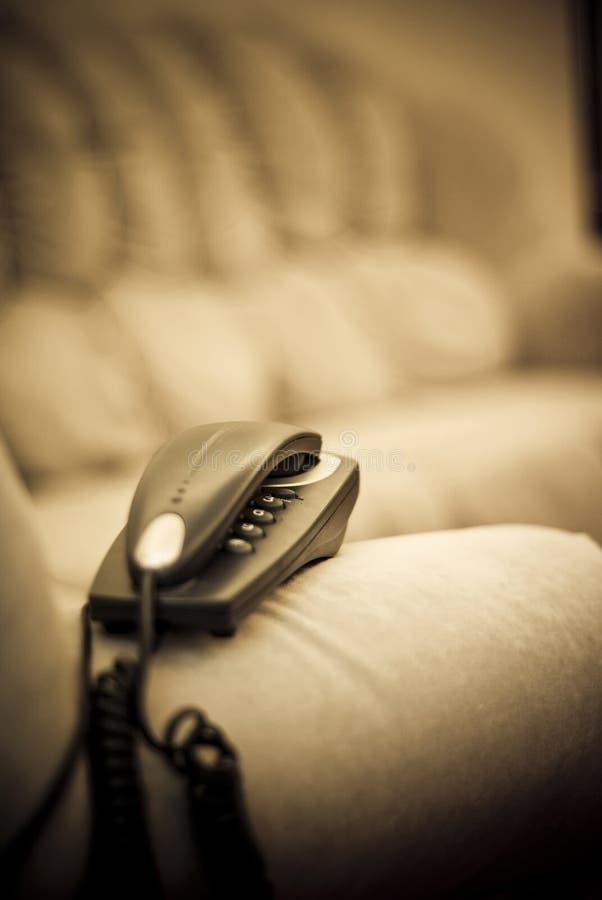 Téléphone à la maison de câble sur le sofa images libres de droits