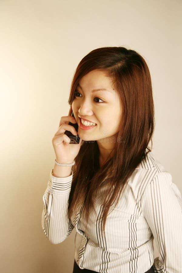 Téléphone asiatique de réponse de dame de bureau photo stock