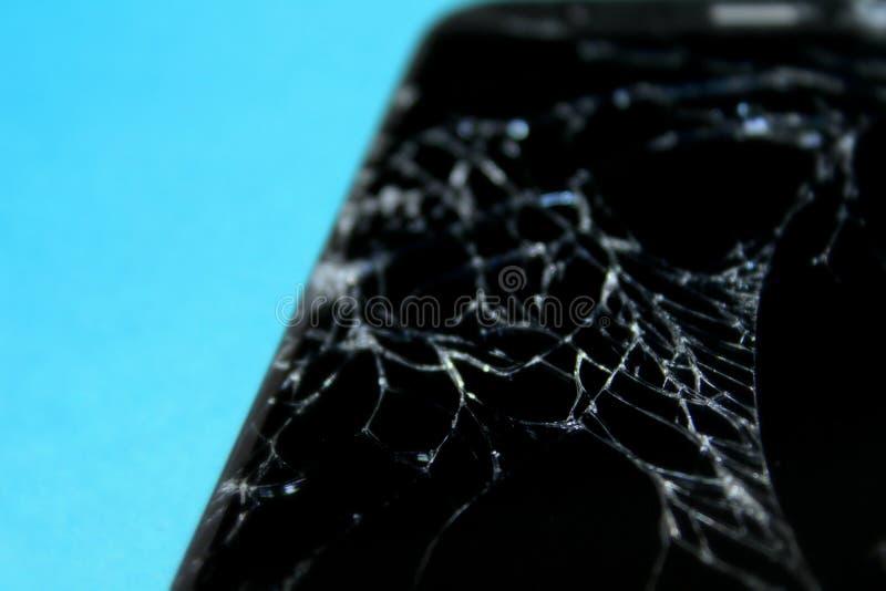 Téléphone cassé sur le fond bleu ?cran criqu? photos stock