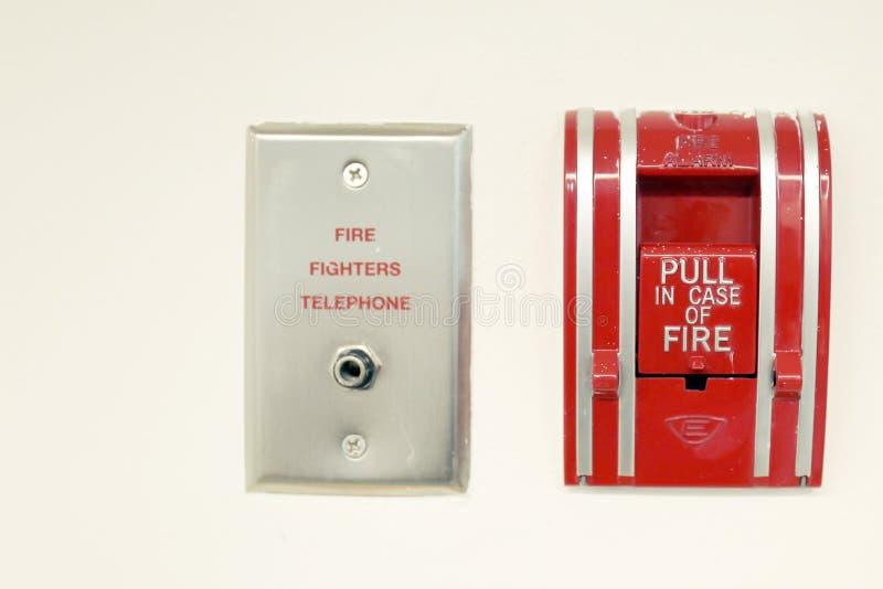 Téléphone d'alarmes d'incendie et de sapeurs-pompiers sur le fond blanc photos stock