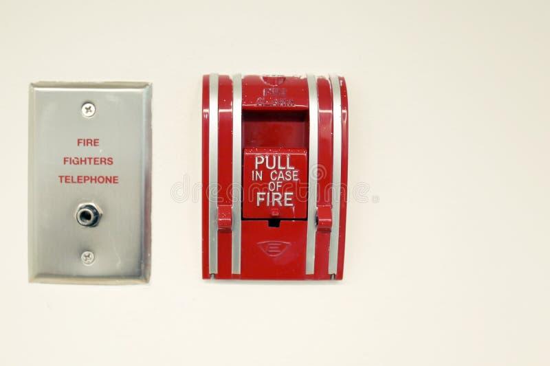 Téléphone d'alarmes d'incendie et de sapeurs-pompiers sur le fond blanc images stock