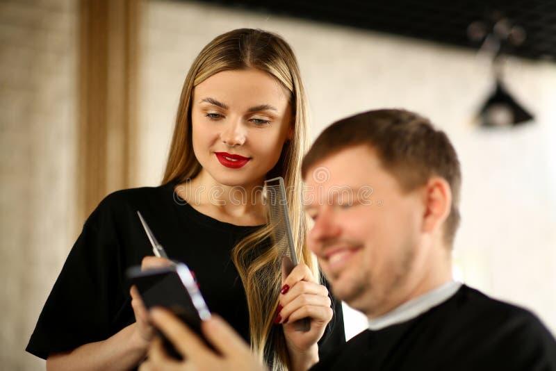 Téléphone d'apparence de client d'homme à la coiffeuse de femme photo libre de droits