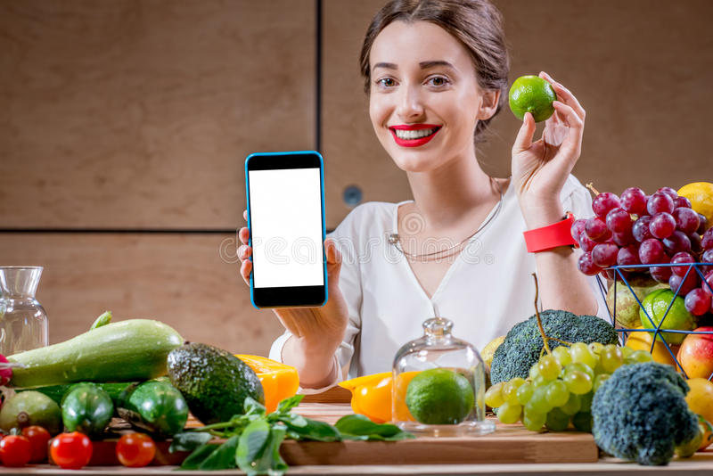 Téléphone d'apparence de femme sur la table complètement de la nourriture saine photo libre de droits