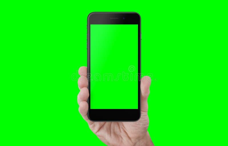 Téléphone d'apparence de main avec l'écran d'isolement et fond en vert photographie stock