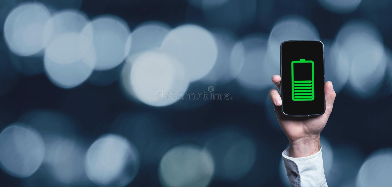 Téléphone d'apparence de main avec l'icône verte de batterie sur l'écran image libre de droits