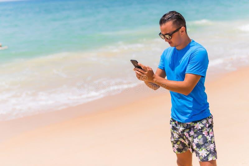Téléphone d'utilisation d'homme sur la dactylographie de la plage ou Internet d'utilisation le jour ensoleillé photographie stock libre de droits