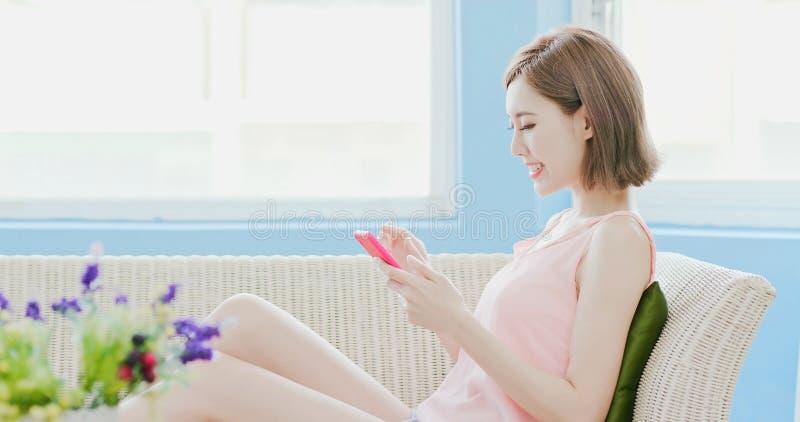 Téléphone d'utilisation de femme heureusement photographie stock