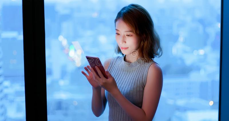 Téléphone d'utilisation de femme heureusement image stock