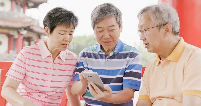 Téléphone d'utilisation de personnes âgées heureusement image libre de droits