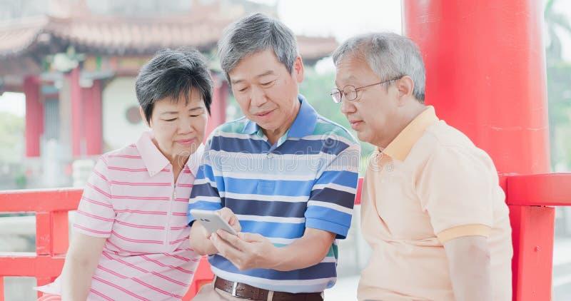 Téléphone d'utilisation de personnes âgées heureusement photographie stock libre de droits