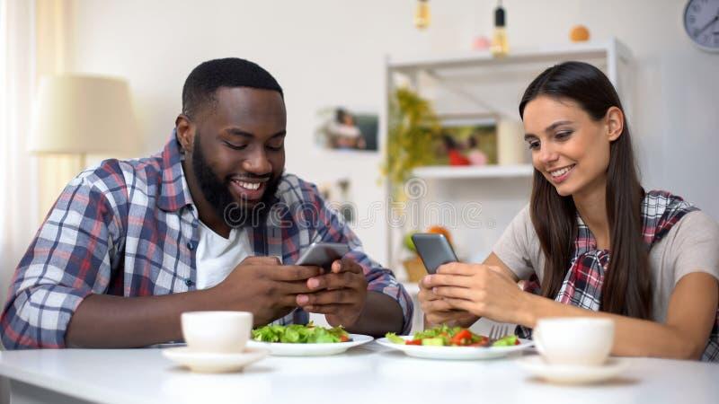 Téléphone de causerie afro-américain d'homme et de femme pendant le déjeuner, manque de communication photo stock