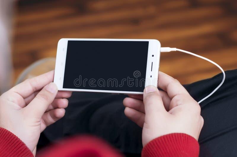 Téléphone de participation d'homme avec des écouteurs reliés image stock
