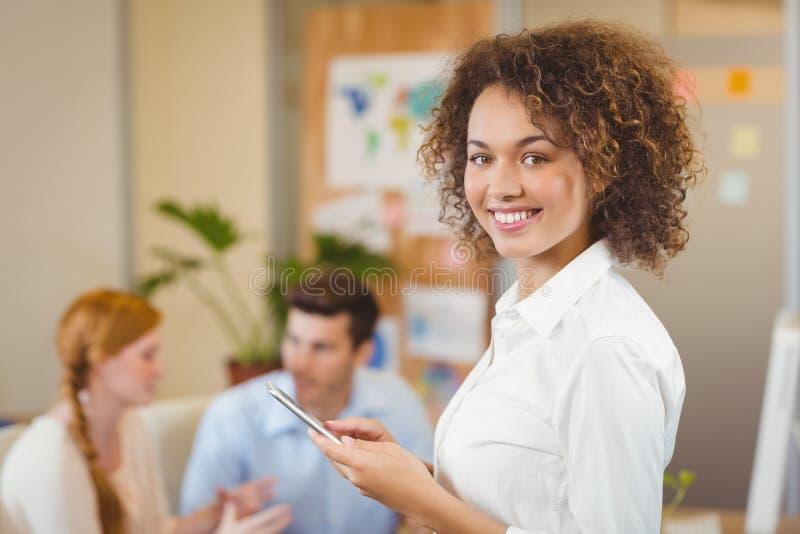 Téléphone de participation de femme d'affaires tandis que travailler de collègues images libres de droits
