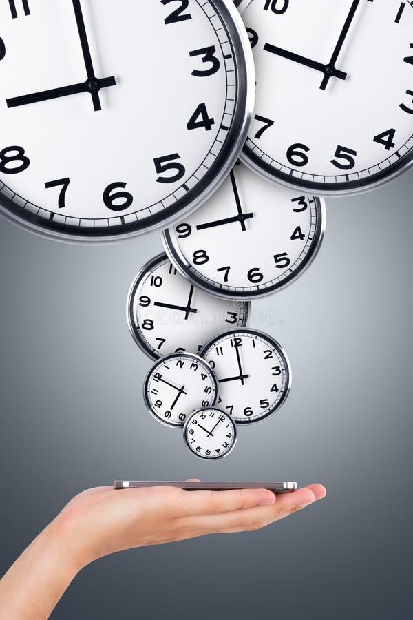 Téléphone de participation de main avec les horloges analogues photo stock