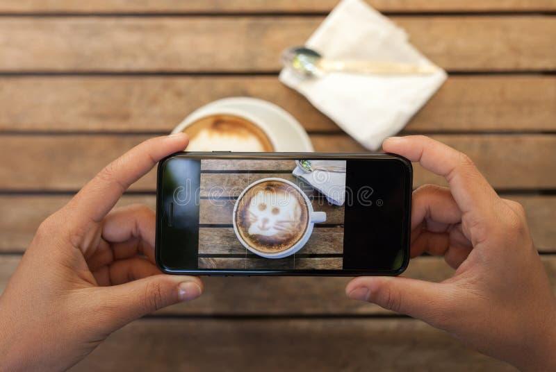 téléphone de participation de main prenant la photo de café sur la table photographie stock