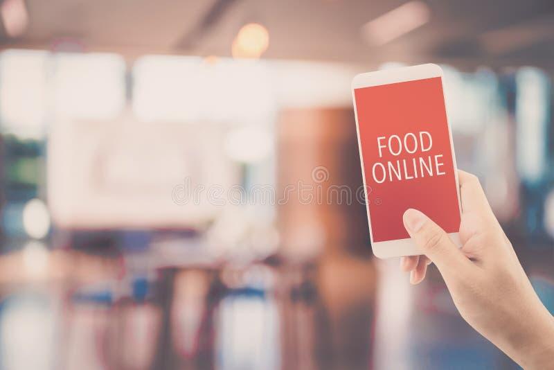 Téléphone de participation de main avec l'ordre de nourriture en ligne avec la tache floue du fond de restaurant image stock