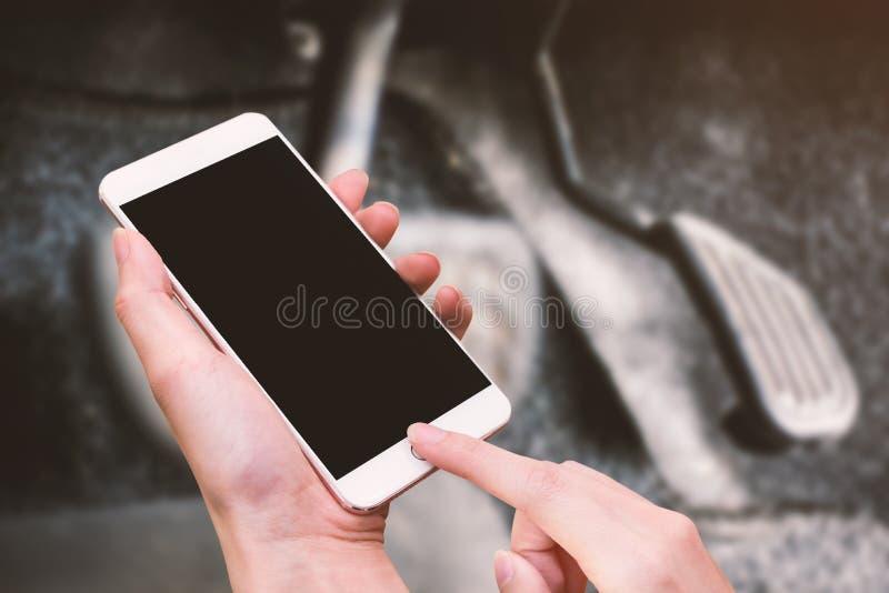 Téléphone de prise de femme et bouton intelligents de contact à la main avec l'écran vide pour la publicité, l'accélérateur et le photo libre de droits