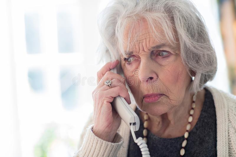 Téléphone de réponse inquiété de femme supérieure à la maison photographie stock libre de droits