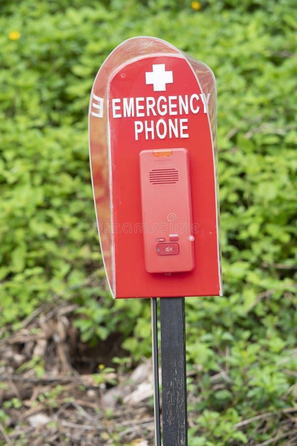 Téléphone de secours ou cabine téléphonique rouge de sécurité près de piscine image libre de droits
