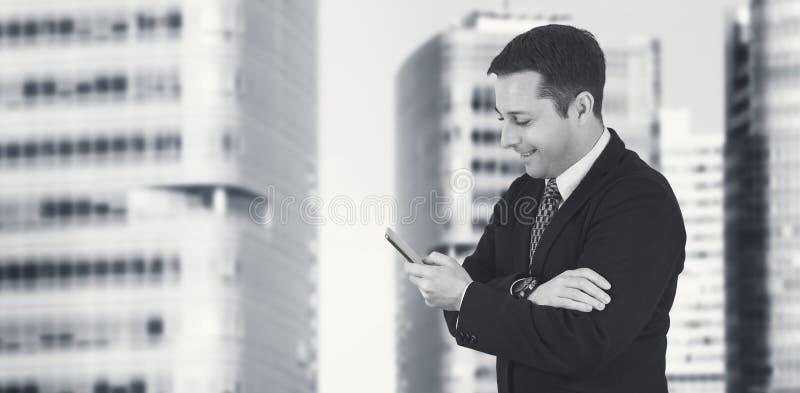 Téléphone de Talking On The d'homme d'affaires avec la ville d'affaires et bâtiments d'entreprise à l'arrière-plan photographie stock libre de droits