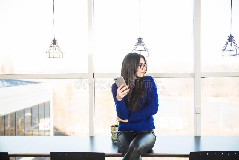Téléphone de wirh de fille dans le bureau moderne images libres de droits