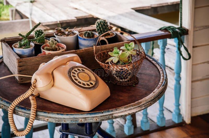 Téléphone en pastel de vintage de rétro vieille rose sur la table en bois avec le cactu photographie stock libre de droits