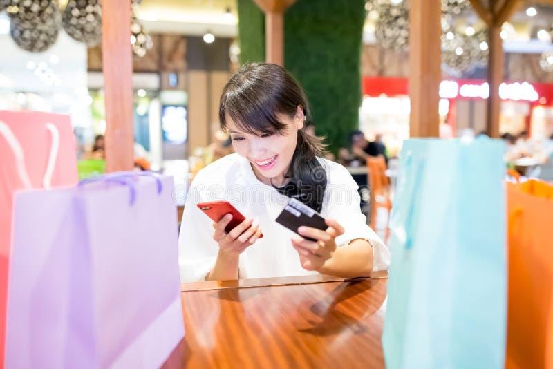 Téléphone et carte d'utilisation de femme photographie stock libre de droits