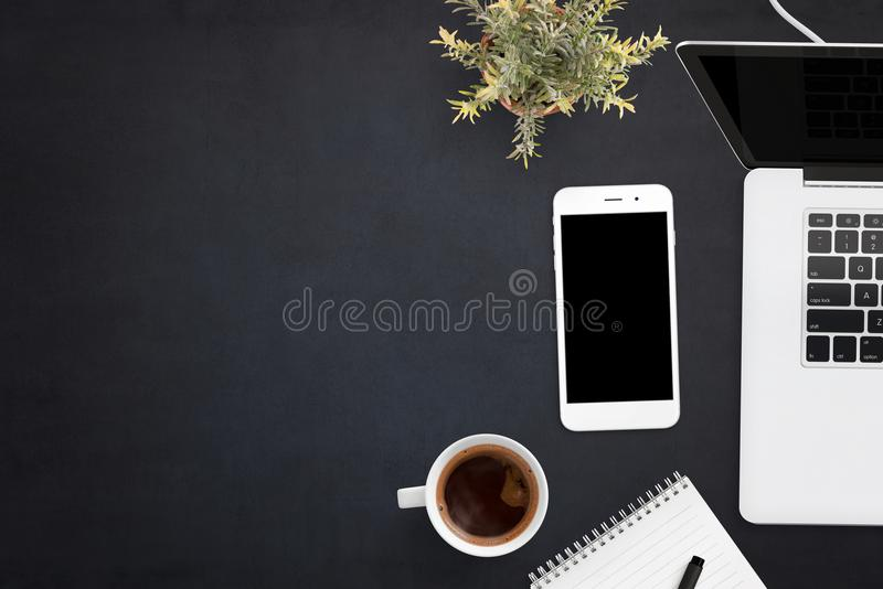 Téléphone et ordinateur portable intelligents sur le bureau noir avec l'espace de copie du côté gauche image stock