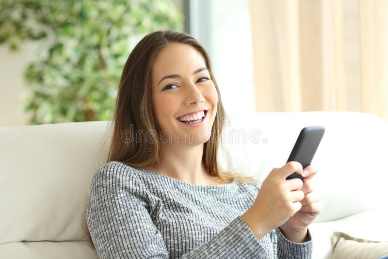 Téléphone heureux de participation de fille et regarder l'appareil-photo images stock