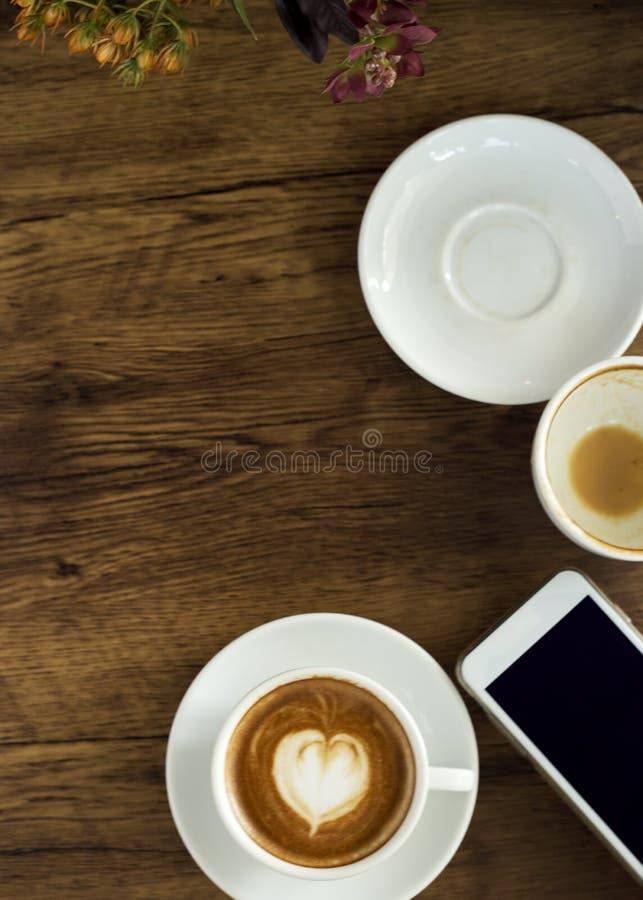 Téléphone intelligent avec du café d'art de latte sur le fond en bois photos stock