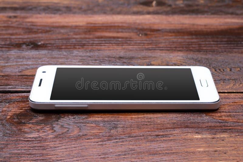 Téléphone intelligent avec l'écran vide se trouvant sur en bois photos stock