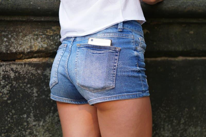 Téléphone intelligent dans la poche arrière de pantalon chaud ou de shorts de butin photo stock
