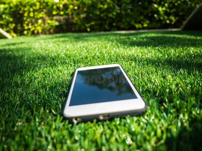 Téléphone intelligent sur un champ d'herbe artificiel photos libres de droits