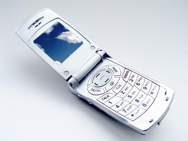 Téléphone mobile avec des nuages photographie stock libre de droits