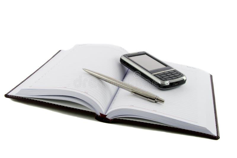 téléphone mobile proche de crayon lecteur de cahier vers le haut images stock