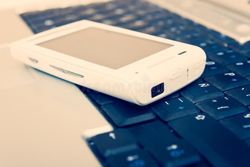Téléphone mobile sur l'ordinateur portatif photo libre de droits
