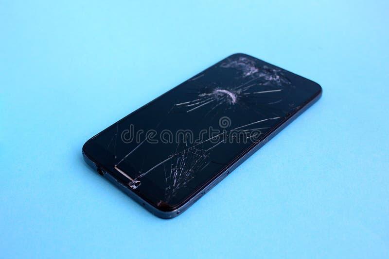 Téléphone noir cassé sur un fond bleu image stock