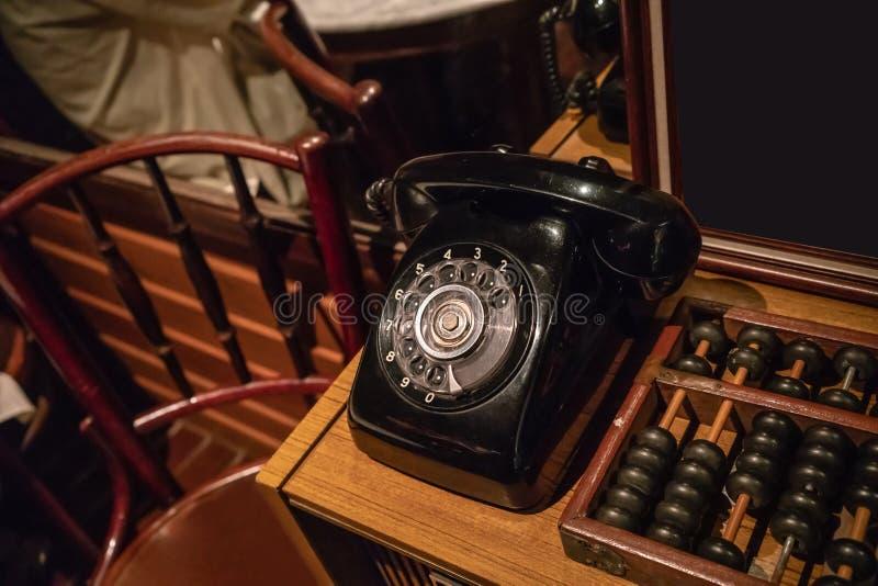 Téléphone noir de vintage sur la table en bois près de l'abaque photographie stock libre de droits