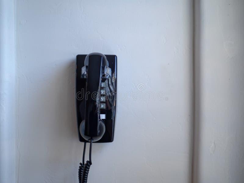 Téléphone noir et récepteur de ligne terrestre accrochant sur le mur blanc photo stock