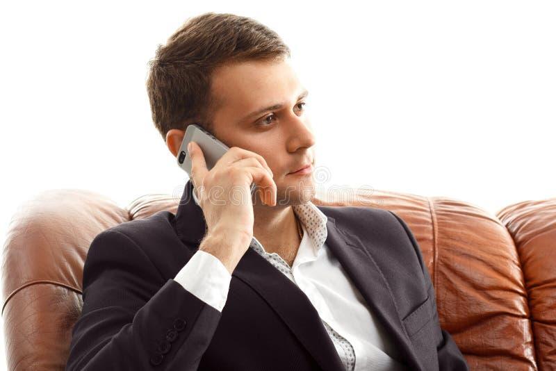 Téléphone parlant d'homme d'affaires se reposant sur le divan photos libres de droits