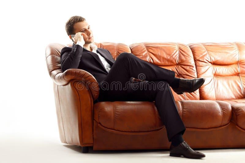 Téléphone parlant d'homme d'affaires se reposant sur le divan images libres de droits
